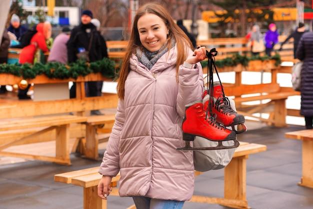 Bela jovem em uma pista de patinação com patins nas mãos