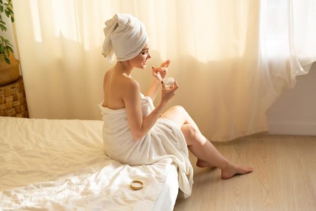 Bela jovem em uma toalha branca na cama no quarto com creme corporal