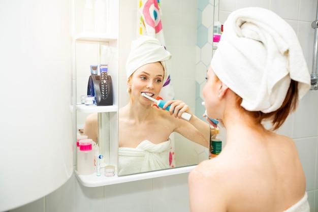 Bela jovem em uma toalha no banheiro escovando os dentes