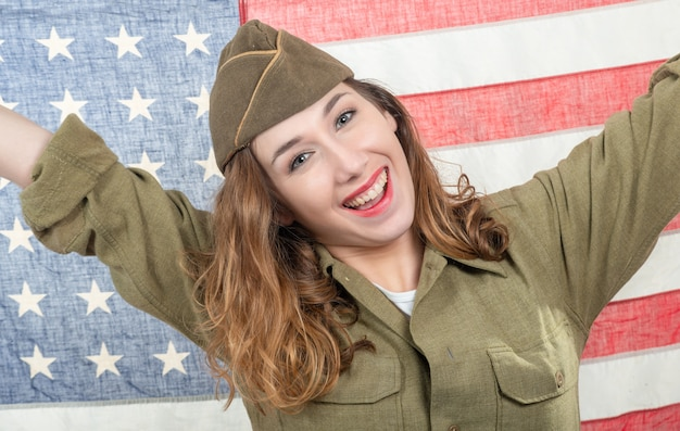 Bela jovem em wwii uniforme nos com a bandeira americana
