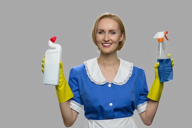Bela jovem empregada doméstica olhando para a câmera. mulher sorridente, mostrando duas garrafas de química para limpar a casa. serviço de limpeza profissional.