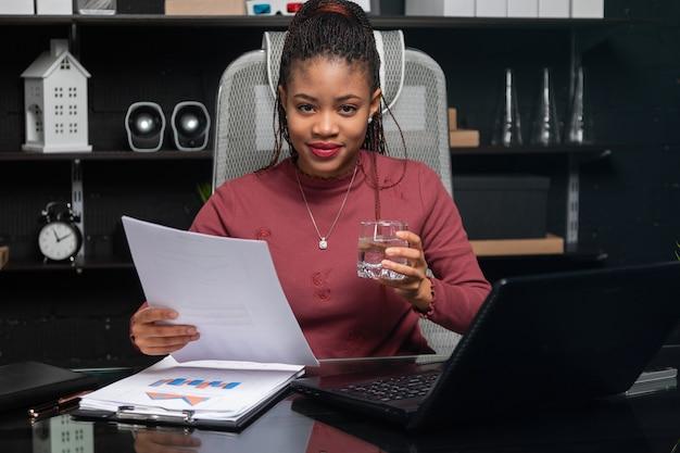 Bela jovem empresária afro-americana, segurando o copo de água e trabalhando com documentos na mesa no escritório
