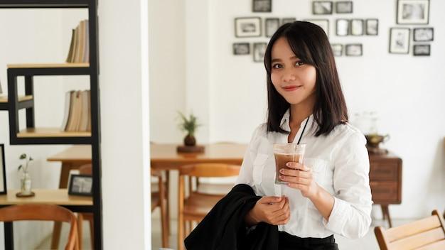 Bela jovem empresária asiática em terno de pé segurando a xícara de café marrom no caffe enquanto faz uma pausa para o café.