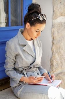 Bela jovem empresária caucasiana tomando notas enquanto está sentada na escada na porta