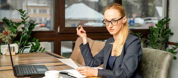 Bela jovem empresária caucasiana trabalhando com documentos em um café