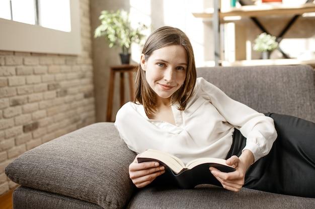 Bela jovem empresária deitado no sofá na sala. ela posa na câmera e sorri. livro aberto de preensão de mulher.