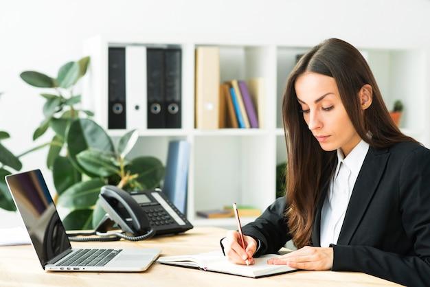 Bela jovem empresária escrevendo com lápis no diário com o laptop sobre a mesa