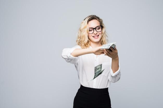 Bela jovem empresária espalhando dinheiro isolado na parede branca