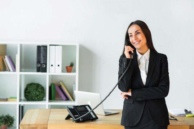 Bela jovem empresária falando no telefone em pé perto da mesa de madeira