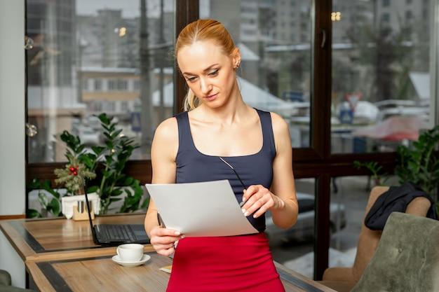 Bela jovem empresária olhando documentos enquanto está no escritório ou no café
