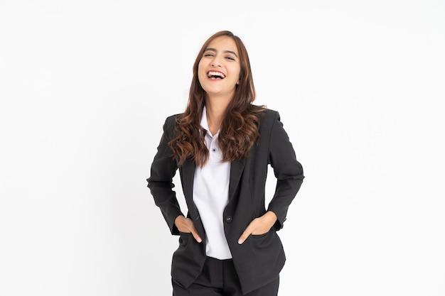 Bela jovem empresária rindo alegremente com as duas mãos nos bolsos