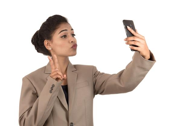 Bela jovem empresária usando smartphone para tirar foto de selfie isolada