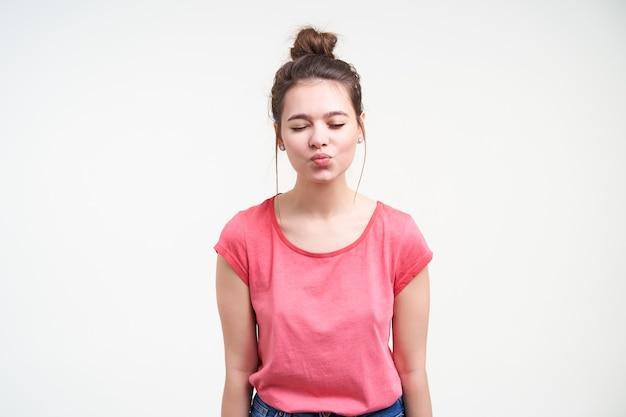 Bela jovem encantadora de cabelos castanhos com maquiagem natural, mantendo os olhos fechados enquanto dobra os lábios no ar beijo, isolado sobre fundo branco
