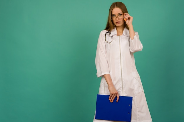 Bela jovem enfermeira ou médica estagiária com pasta azul e estatoscópio em um espaço azul