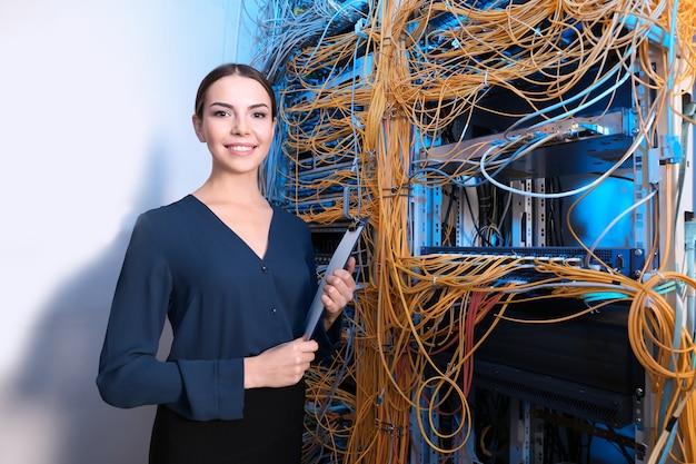 Bela jovem engenheira com a área de transferência na sala do servidor