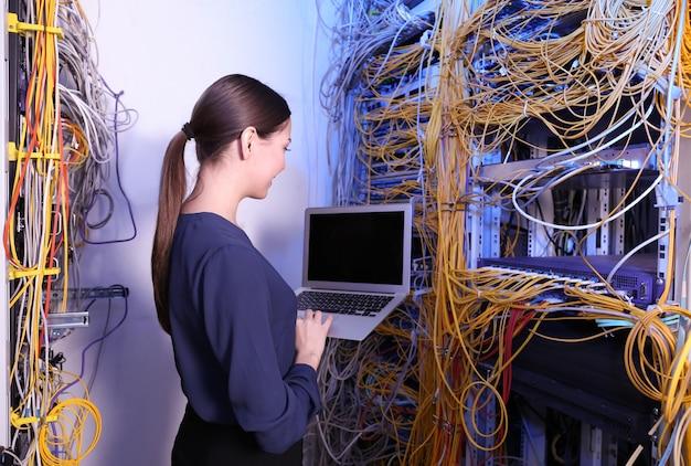 Bela jovem engenheira com laptop na sala do servidor