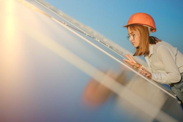 Bela jovem engenheira em pé perto de painéis solares ao ar livre, o conceito de energia verde.