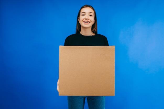 Bela jovem entregadora carregando uma caixa de papelão em branco
