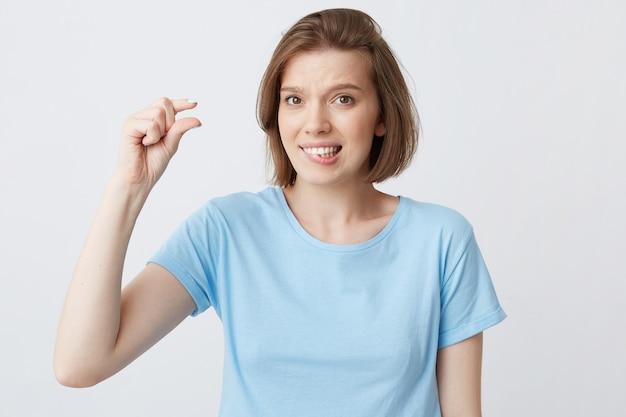 Bela jovem envergonhada de camiseta azul mordendo o lábio e mostrando o tamanho minúsculo com os dedos