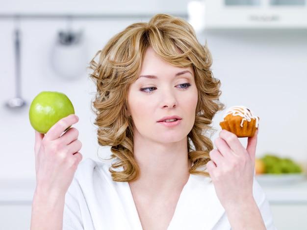 Bela jovem escolhe entre bolo doce e maçã verde
