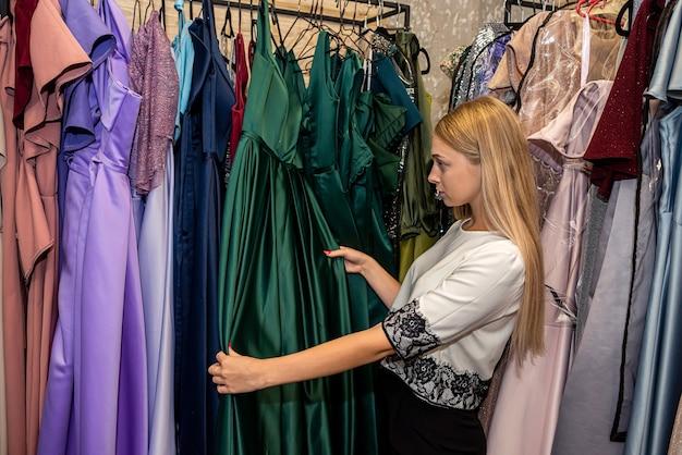 Bela jovem escolhendo elegante vestido de noite na loja de roupas. moda