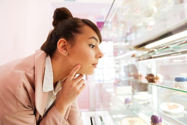 Bela jovem escolhendo pastelaria enquanto olha através da vitrine de vidro