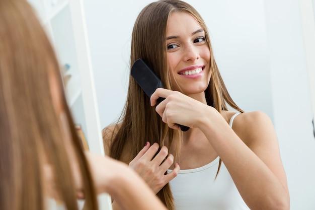Bela jovem escovando seus longos cabelos na frente do espelho.