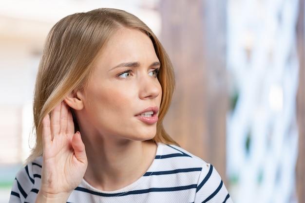Bela jovem escutando fofocas e segurando a mão perto da orelha
