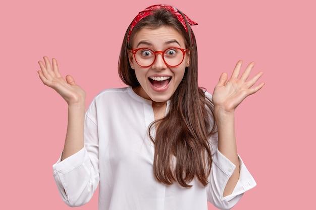 Bela jovem espantada levanta as palmas das mãos, sorri amplamente, reage ao receber palavras agradáveis