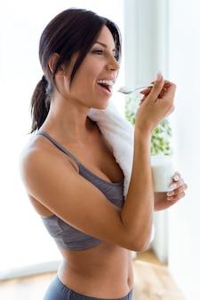 Bela jovem esportiva comendo iogurte em casa.