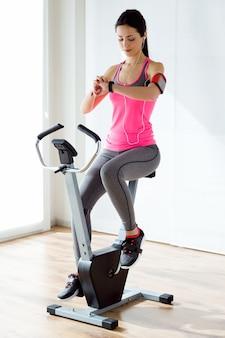 Bela jovem esportiva fazendo exercício na academia.