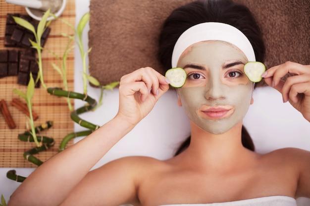 Bela jovem está a máscara facial de argila no spa