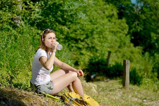 Bela jovem está descansando durante uma caminhada nas montanhas