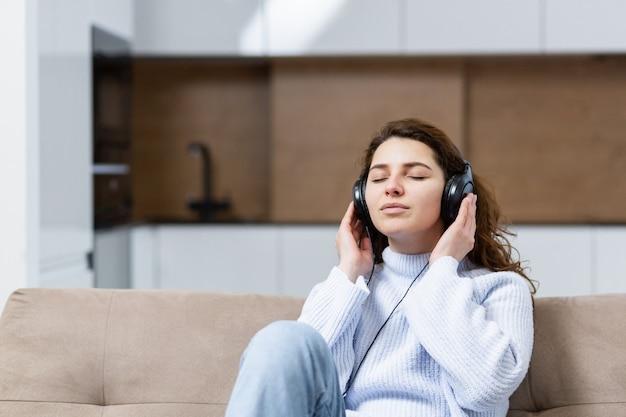 Bela jovem está descansando em casa, sentada no sofá e ouvindo música em fones de ouvido