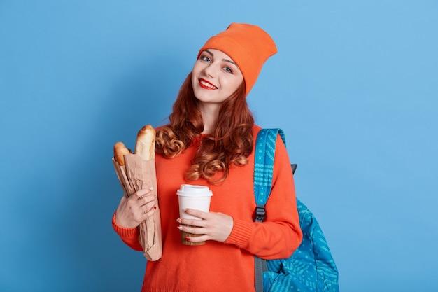 Bela jovem estudante com mochila nas costas e café para viagem