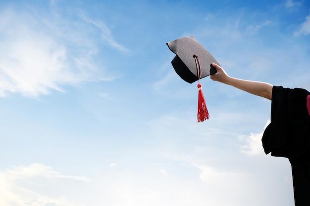Bela jovem estudante em túnica preta, levantando-se com os braços na mão, chapéu e certificado.
