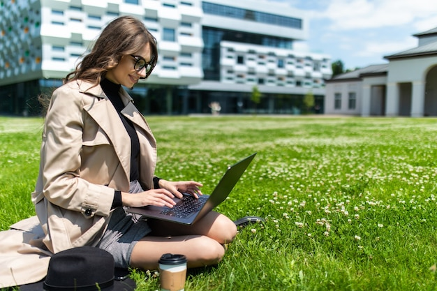 Bela jovem estudante usando laptop na grama do campus