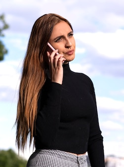 Bela jovem fala em seu telefone enquanto seu rosto é sério
