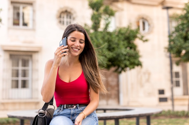 Bela jovem falando ao telefone de frente