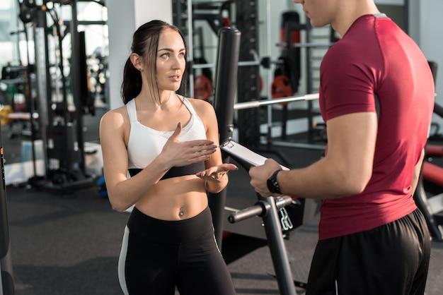Bela jovem falando com o treinador de fitness