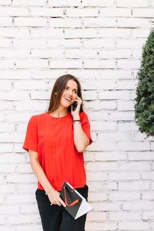 Bela jovem falando no celular em frente a parede de tijolos