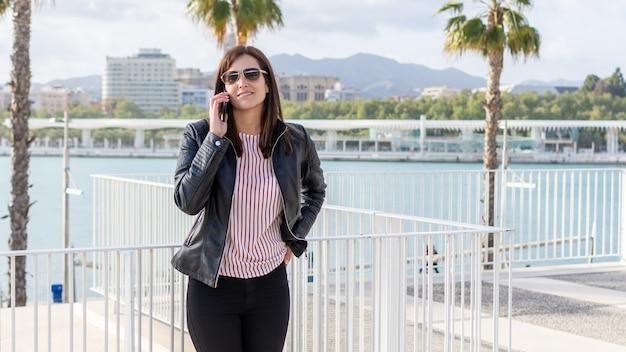 Bela jovem falando no celular em málaga, um dia ensolarado