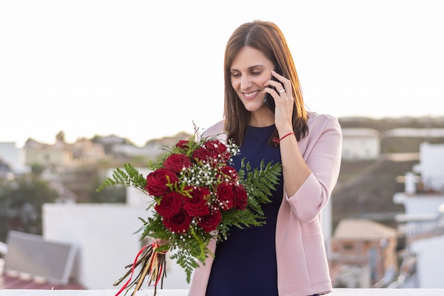 Bela jovem falando no telefone com buquê de rosas vermelhas