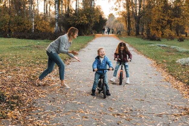 Bela jovem família brincando ao ar livre no parque, enquanto filha e filho está andando de bicicleta e a mãe está dando o início.