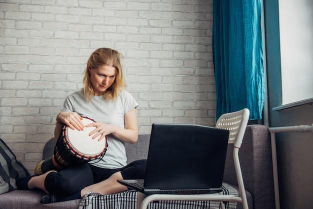 Bela jovem faz música tocando o djembe, olhando para o laptop. curso on-line remoto de tocar bateria