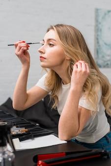 Bela jovem fazendo ela mesma maquiagem sentado no estúdio