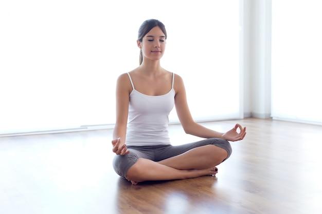 Bela jovem fazendo exercícios de ioga em casa.