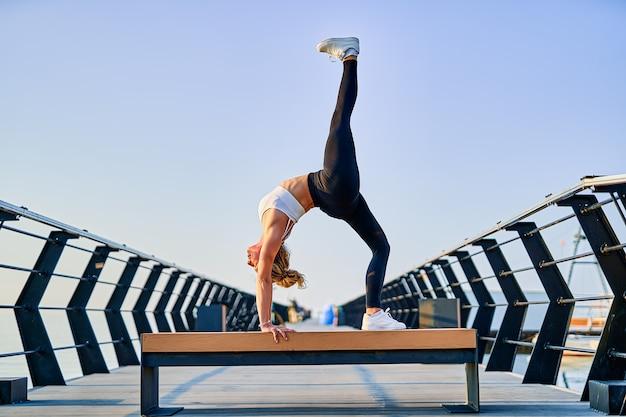 Bela jovem fazendo exercícios de ioga na natureza pela manhã