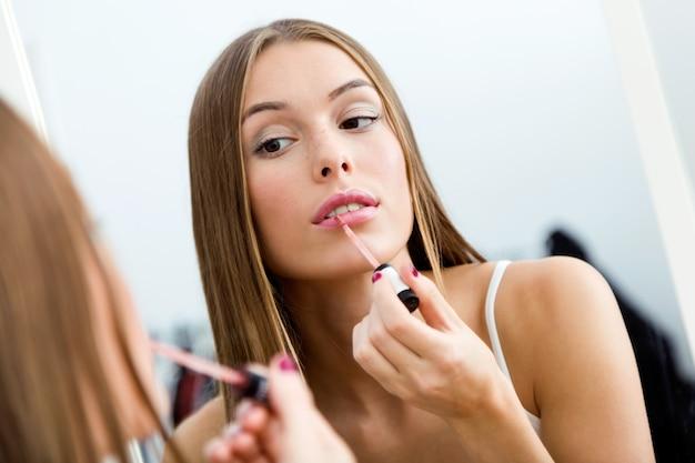 Bela jovem fazendo maquiagem perto do espelho em casa.