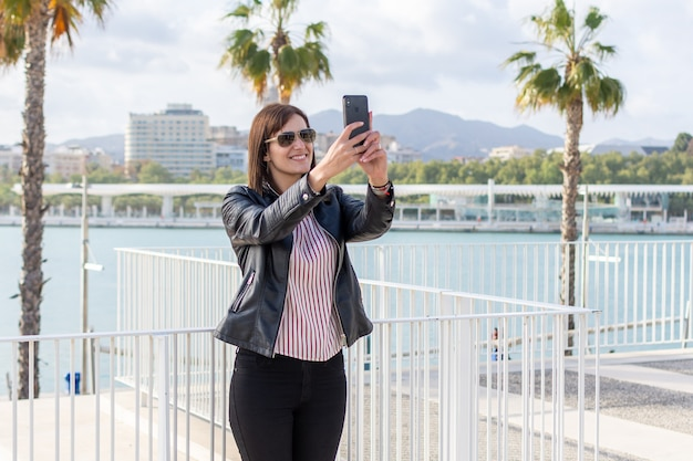 Bela jovem fazendo um selfie com seu telefone celular em málaga, um dia ensolarado